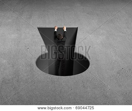 Man Climbing Out From Key Shape Hole