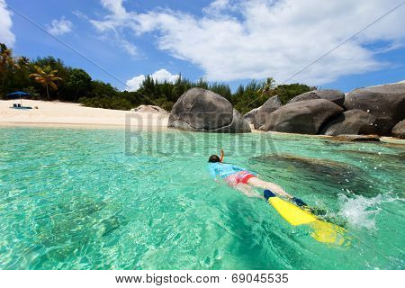 Young woman in sun protection swimwear snorkeling in turquoise tropical water at exotic island beach