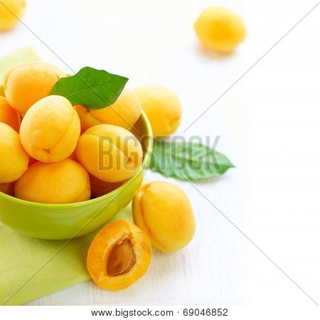 Apricot. Ripe Organic Apricots with leaves on a white wooden table