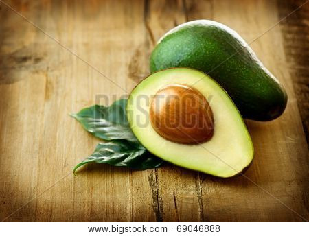 Avocado. Organic Avocados with leaves on a wooden table. Healthy Vegan food concept. Diet. Dieting
