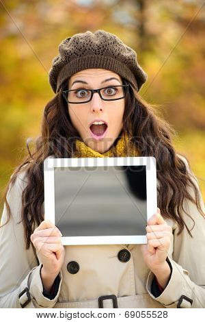 Surprised Woman Showing Digital Tablet Screen In Autumn