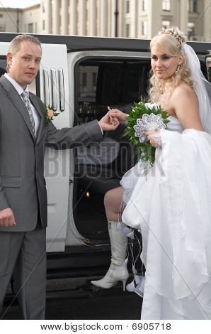 Bride and groom stand near a car