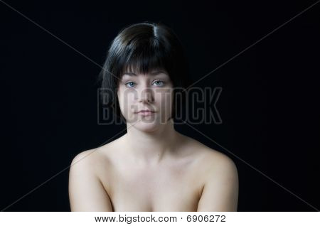 Beautiful topless caucasian woman with bright blue eyes on black background