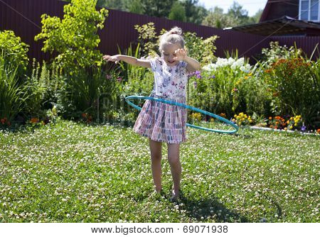 Happy little girl playing with hula hoop in her garden