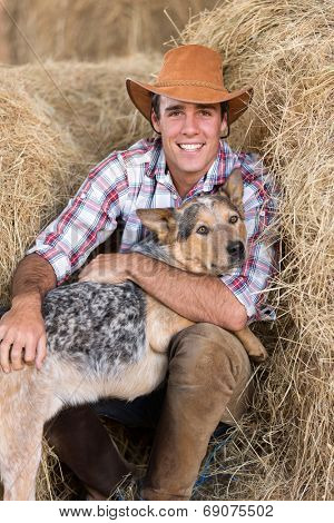 portrait of cowboy with his dog sitting on hay
