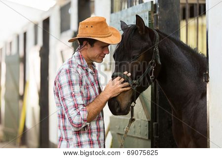 young horse breeder comforting a horse in stable