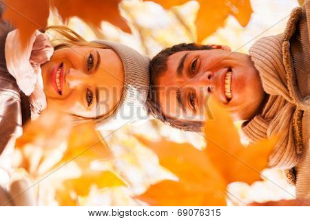 underneath view of happy young couple in autumn park