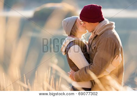 loving young couple kissing by the lake in winter morning