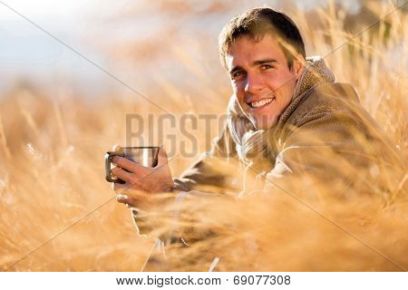 cheerful young man drinking coffee outdoors in fall
