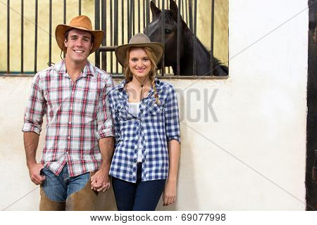 happy cowboy and cowgirl couple holding hands inside stables
