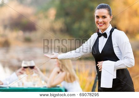 pretty young waitress welcomes customers to romantic dinning environment