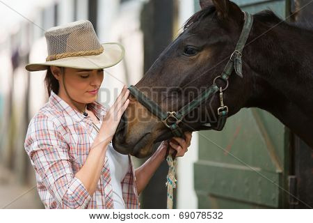 caring cowgirl talking to a horse in farm house