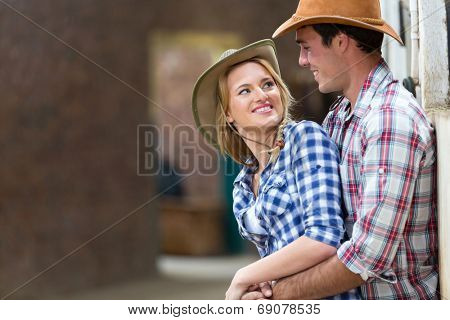 happy young farm couple embracing in stables