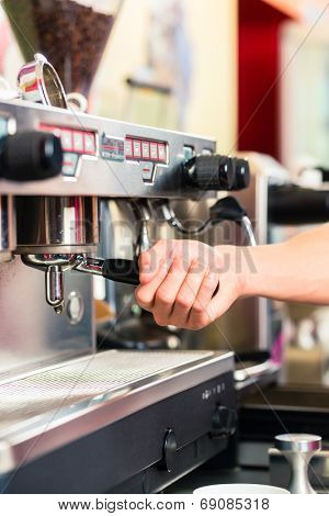 Barista using coffee machine or unit and preparing espresso or cappuccino in coffeehouse or shop