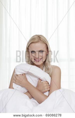 Portrait of attractive young woman holding bedsheet in bed
