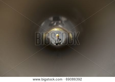 View of confident male architect through large pipe at construction site