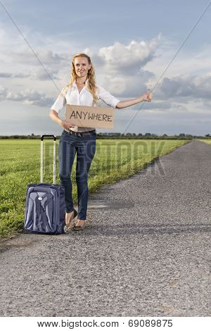 Full length of woman hitching while holding anywhere sign on countryside