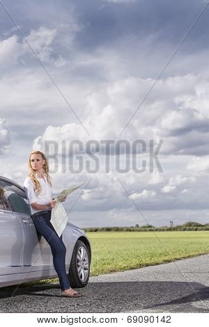 Full length of mid adult woman leaning on car while holding map at countryside