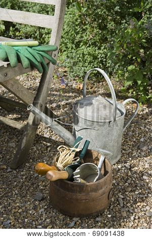 Closeup of gardening tools and chair in the garden