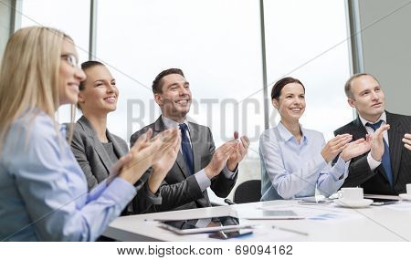business, technology and office concept - happy business team with laptop computers, documents and coffee clapping hand