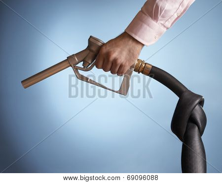 Closeup side view of a hand holding fuel pump with knot in pipe against blue background
