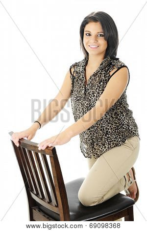 A happy teen girl with one leg kneeling on a tall chair.  On a white background.