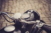 pic of cobblestone  - a motorcycle handlebar with a brownshaded cobblestone pavement - JPG