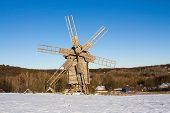 pic of snowy hill  - Wooden flour mill on a snowy hill on a sunny winter day - JPG