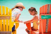 picture of upset  - Mother talking to upset little daughter while sitting on colorful wooden chairs at tropical beach during summer vacation - JPG