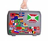 stock photo of burundi  - Used plastic suitcase with lots of small stickers large sticker of Burundi - JPG