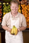 picture of grocery store  - A man working at a grocery store holding out some bananas - JPG