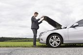 picture of hoods  - Full length side view of young businessman opening broken down car hood at countryside - JPG