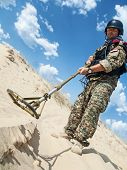 pic of landmines  - iraqi soldier in the desert with army metal detector - JPG