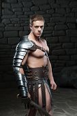 picture of sparta  - Waistup side view portrait of young attractive warrior gladiator with muscular body posing with sword on dark background - JPG