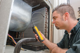 image of coil  - An Hvac technician searching for a refrigerant leak on an evaporator coil - JPG