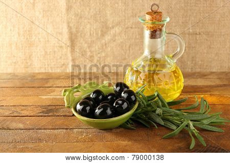 Black marinated olives in green saucepan with oil near branch and oilcan on rustic wooden background