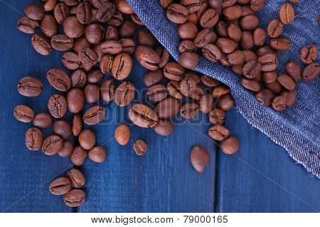 Spilled coffee beans on blue wooden background with jeans material