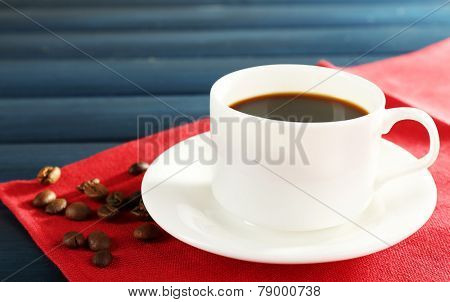 Cup of coffee on red napkin with coffee beans color wooden background