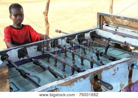 Unidentified Young Boys Play Table Soccer.
