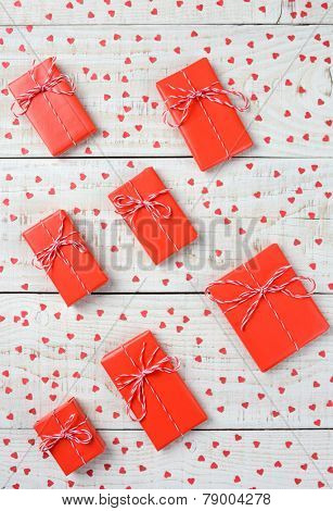 Overhead shot of a group of Valentines Day presents wrapped in red paper tied with string and surrounded by mini red paper hearts on a rustic wood table. Vertical format.