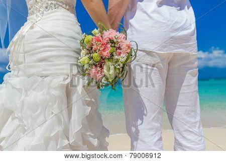 beautiful wedding bouquet in bride and groom hands, outdoor beach wedding