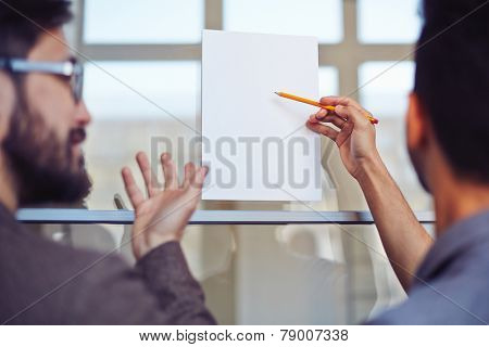 Male manager pointing at blank paper on noticeboard with pencil