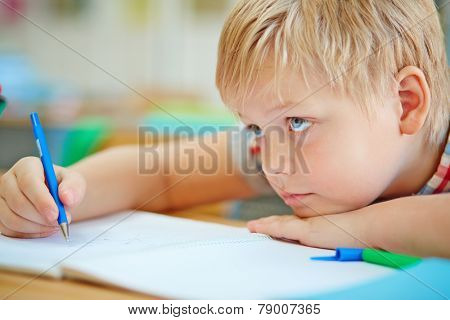Little learner writing in copybook at lesson