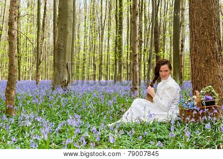 Victorian woman in white dress in a springtime bluebells forest