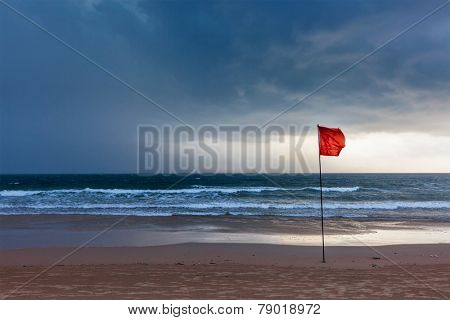 Danger concept background - severe storm warning flags on beach. Baga, Goa, India