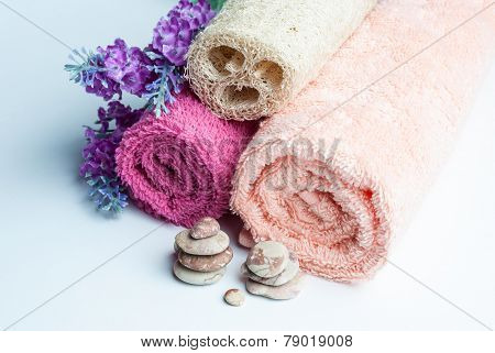 Spa towels rolls flower and stones lying on shite background. Horizontal composition.