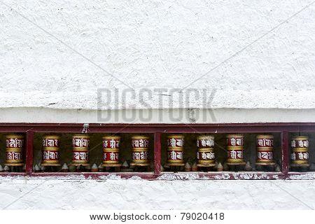 Prayer wheels on white wall