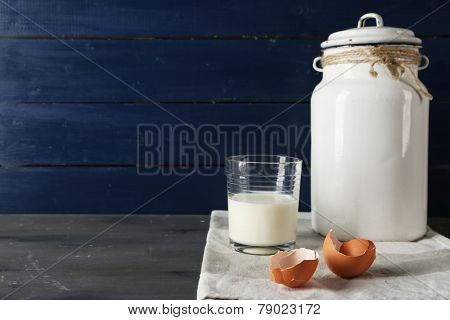 Milk can with glass and eggshell on color wooden background