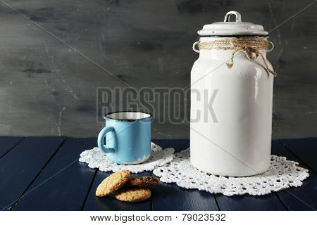 Milk can and cup with cookies on lace doily on wooden table and dark background