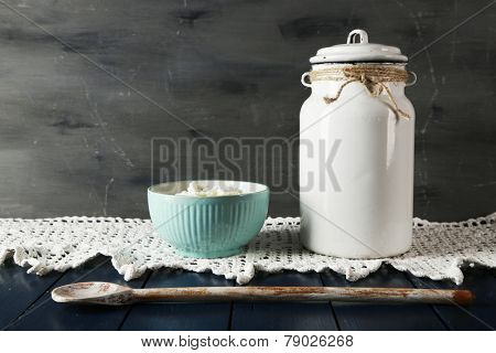 Milk can with bowl of cottage cheese on lace doily on wooden table and dark background